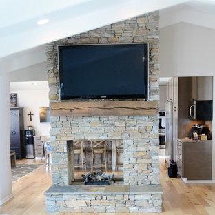 Imagen de salón abierto, campestre, grande, con suelo de madera en tonos medios, paredes blancas, chimenea de doble cara, marco de chimenea de piedra, televisor colgado en la pared y suelo marrón