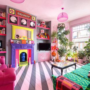 Immagine di un soggiorno eclettico di medie dimensioni con pareti rosa, pavimento in legno verniciato, camino classico, TV autoportante e pavimento multicolore