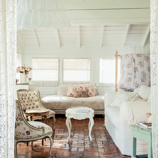 This is an example of a shabby-chic style enclosed living room in Los Angeles with white walls and brick floors.