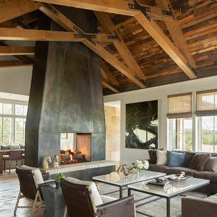 Immagine di un soggiorno stile rurale aperto con pareti bianche, pavimento in legno massello medio, camino bifacciale, cornice del camino in metallo e pavimento marrone