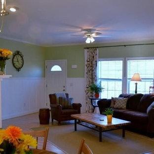 Modelo de salón abierto, de estilo de casa de campo, de tamaño medio, con paredes verdes, suelo laminado, chimenea tradicional, marco de chimenea de madera y suelo rosa