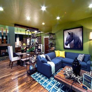 Idee per un piccolo soggiorno country aperto con pareti verdi, pavimento in legno massello medio, camino bifacciale, cornice del camino in pietra e TV a parete