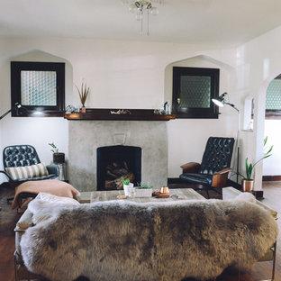 Immagine di un soggiorno boho chic di medie dimensioni e chiuso con pareti bianche, pavimento in legno massello medio, camino classico, cornice del camino in cemento e nessuna TV