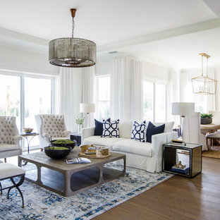 Example of a transitional formal and open concept medium tone wood floor living room design in Jacksonville with white walls