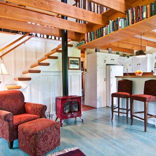 Ispirazione per un piccolo soggiorno eclettico aperto con libreria, stufa a legna e pavimento blu