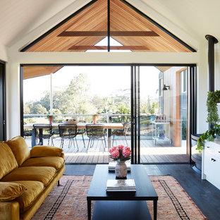 Foto di un soggiorno stile marinaro con pareti bianche, parquet scuro, stufa a legna, cornice del camino in metallo, TV a parete e pavimento nero