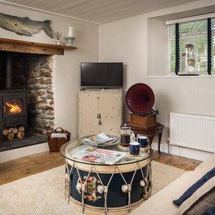 コーンウォールの中サイズのビーチスタイルのおしゃれな独立型リビング (フォーマル、白い壁、無垢フローリング、薪ストーブ、石材の暖炉まわり、据え置き型テレビ) の写真