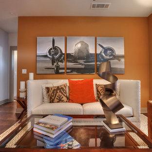 Modelo de salón abierto, clásico renovado, pequeño, con parades naranjas, suelo de madera oscura y televisor colgado en la pared