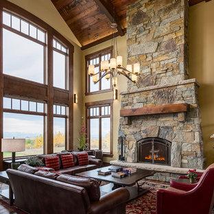 Неиссякаемый источник вдохновения для домашнего уюта: большая открытая гостиная комната в стиле рустика с желтыми стенами, паркетным полом среднего тона, стандартным камином, фасадом камина из камня и коричневым полом без ТВ