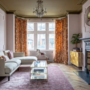 Inspiration for a victorian living room in London with light hardwood floors, a standard fireplace, no tv and pink walls.