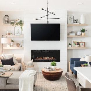 バンクーバーの小さい北欧スタイルのおしゃれなLDK (白い壁、クッションフロア、吊り下げ式暖炉、塗装板張りの暖炉まわり、壁掛け型テレビ、マルチカラーの床) の写真