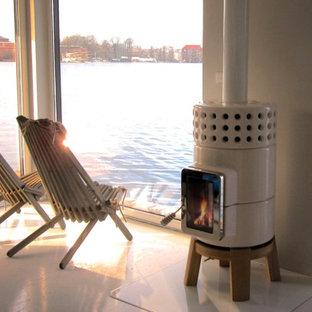 ポートランド(メイン)の小さい北欧スタイルのおしゃれなLDK (ライブラリー、白い壁、リノリウムの床、薪ストーブ、コンクリートの暖炉まわり、白い床) の写真