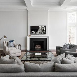 Idée de décoration pour un grand salon tradition ouvert avec un sol en bois foncé, un sol marron, un plafond à caissons, une salle de réception, un mur gris, une cheminée standard, un manteau de cheminée en pierre et un téléviseur fixé au mur.