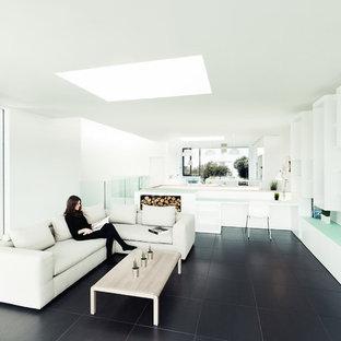 Immagine di un soggiorno contemporaneo aperto con pareti bianche, stufa a legna e pavimento nero