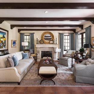 ロサンゼルスの大きい地中海スタイルのおしゃれな独立型リビング (フォーマル、ベージュの壁、磁器タイルの床、標準型暖炉、石材の暖炉まわり、テレビなし、茶色い床) の写真