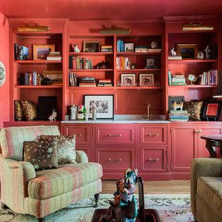 Immagine di un soggiorno chic chiuso e di medie dimensioni con libreria, pareti rosse, pavimento in legno massello medio, camino classico, cornice del camino in pietra, TV a parete e pavimento marrone