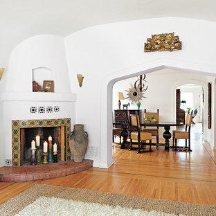 Ispirazione per un soggiorno mediterraneo con pareti bianche, pavimento in legno massello medio, camino ad angolo e cornice del camino piastrellata