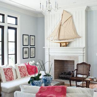 Foto di un soggiorno tropicale con pareti blu e camino classico