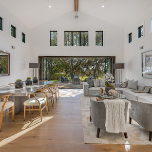 Idée de décoration pour un salon champêtre avec un mur blanc, un sol en bois brun et un sol marron.