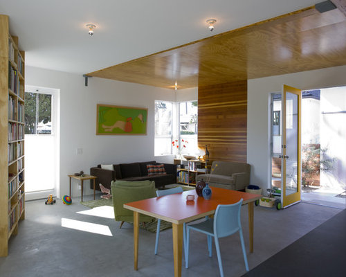 Example Of A Minimalist Living Room Design In Los Angeles With White Walls And Concrete Floors