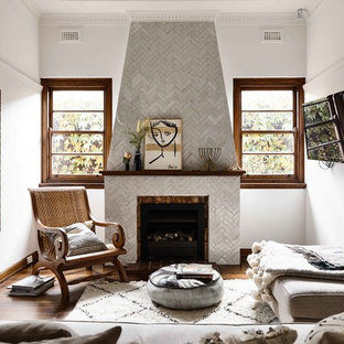 Modelo de salón cerrado, mediterráneo, con paredes blancas, suelo de madera oscura, chimenea tradicional, marco de chimenea de baldosas y/o azulejos, televisor colgado en la pared y suelo marrón