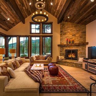 シアトルの大きいラスティックスタイルのおしゃれな独立型リビング (ベージュの壁、淡色無垢フローリング、コーナー設置型暖炉、石材の暖炉まわり、据え置き型テレビ) の写真