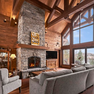 Inspiration for a medium sized rustic open plan living room in Montreal with brown walls, dark hardwood flooring, a stone fireplace surround, a freestanding tv, brown floors and a standard fireplace.