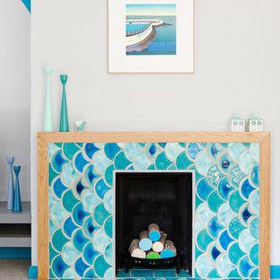 ケンブリッジシャーの大きいコンテンポラリースタイルのおしゃれな独立型リビング (カーペット敷き、据え置き型テレビ、グレーの壁、標準型暖炉、タイルの暖炉まわり、グレーの床) の写真