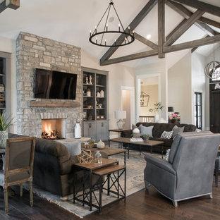 Idee per un ampio soggiorno classico aperto con pareti beige, parquet scuro, camino classico, cornice del camino in pietra, TV a parete e pavimento marrone