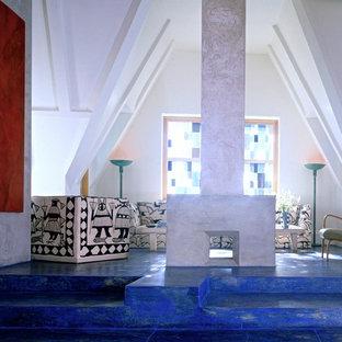 Modelo de salón para visitas tipo loft, minimalista, grande, sin televisor, con paredes blancas, suelo de cemento, chimenea de doble cara, marco de chimenea de yeso y suelo azul