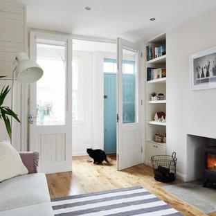 Foto de salón abierto, nórdico, pequeño, sin televisor, con paredes blancas, suelo de madera clara, estufa de leña, marco de chimenea de yeso y suelo marrón