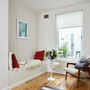 Diseño de biblioteca en casa abierta, nórdica, pequeña, sin televisor, con paredes blancas, suelo de madera clara, estufa de leña, marco de chimenea de yeso y suelo marrón