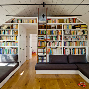 Exempel på ett lantligt vardagsrum, med ett bibliotek, vita väggar och mellanmörkt trägolv