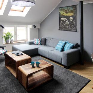 Aménagement d'un petit salon contemporain fermé avec une salle de réception, un mur gris et un sol en bois clair.