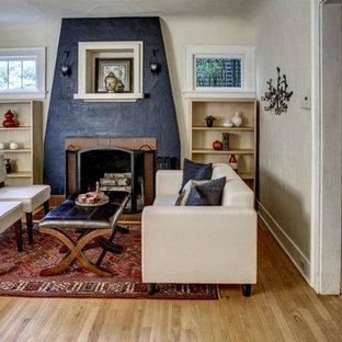 Inredning av ett klassiskt vardagsrum, med beige väggar, mellanmörkt trägolv och en standard öppen spis