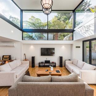 Ejemplo de salón para visitas cerrado, contemporáneo, con paredes blancas, suelo de madera en tonos medios, televisor colgado en la pared y suelo naranja