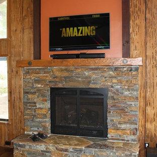 サクラメントの大きいラスティックスタイルのおしゃれなLDK (フォーマル、オレンジの壁、無垢フローリング、標準型暖炉、石材の暖炉まわり、壁掛け型テレビ) の写真