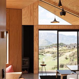 Foto de salón abierto, contemporáneo, pequeño, con suelo de cemento, estufa de leña y televisor colgado en la pared