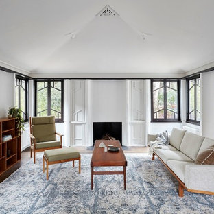 Inspiration for a midcentury formal living room in Melbourne with white walls, dark hardwood floors, a standard fireplace and no tv.