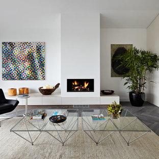 Diseño de salón abierto, actual, de tamaño medio, con paredes blancas, suelo de madera oscura, chimenea tradicional, marco de chimenea de yeso y suelo gris