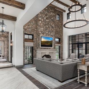 フェニックスの巨大なシャビーシック調のおしゃれなLDK (フォーマル、マルチカラーの壁、無垢フローリング、標準型暖炉、石材の暖炉まわり、壁掛け型テレビ、マルチカラーの床) の写真