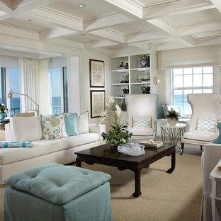 マイアミの大きいビーチスタイルのおしゃれなLDK (白い壁、トラバーチンの床、標準型暖炉、木材の暖炉まわり、壁掛け型テレビ) の写真