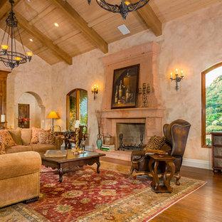 Cette photo montre un très grand salon méditerranéen ouvert avec une salle de réception, un mur beige, un sol en bois brun, une cheminée standard, un téléviseur dissimulé, un manteau de cheminée en béton et un sol marron.