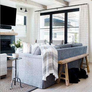 Exemple d'un salon bord de mer de taille moyenne et ouvert avec un mur blanc, un sol en bois clair, une cheminée standard, un manteau de cheminée en carrelage, un téléviseur fixé au mur et un sol beige.