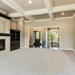 This is an example of a traditional formal open concept living room in Other with grey walls, cork floors, a standard fireplace, a stone fireplace surround, a built-in media wall and grey floor.
