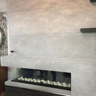 Imagen de biblioteca en casa tipo loft, moderna, grande, con paredes grises, suelo de baldosas de cerámica, chimenea de esquina, marco de chimenea de piedra y suelo beige