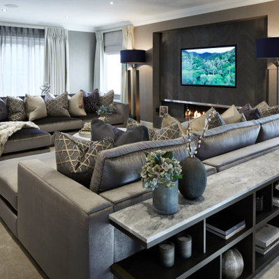 Large trendy enclosed carpeted and gray floor living room photo in Surrey with gray walls, a hanging fireplace, a wood fireplace surround and a wall-mounted tv