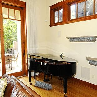 サンディエゴの中くらいのトロピカルスタイルのおしゃれなLDK (ベージュの壁、淡色無垢フローリング、標準型暖炉、漆喰の暖炉まわり、埋込式メディアウォール、茶色い床) の写真