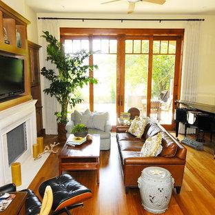 サンディエゴの中サイズのトロピカルスタイルのおしゃれなLDK (ベージュの壁、淡色無垢フローリング、標準型暖炉、漆喰の暖炉まわり、埋込式メディアウォール、茶色い床) の写真