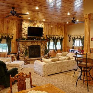 ミネアポリスのラスティックスタイルのおしゃれなLDK (ベージュの壁、カーペット敷き、標準型暖炉、石材の暖炉まわり、壁掛け型テレビ、ベージュの床) の写真